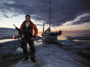 Explorer pose, with; gun, ship, campfire and sunset.  40 miles offshore on a 10 acre ice flow.  Note the kite camera floating behind Empiricus.