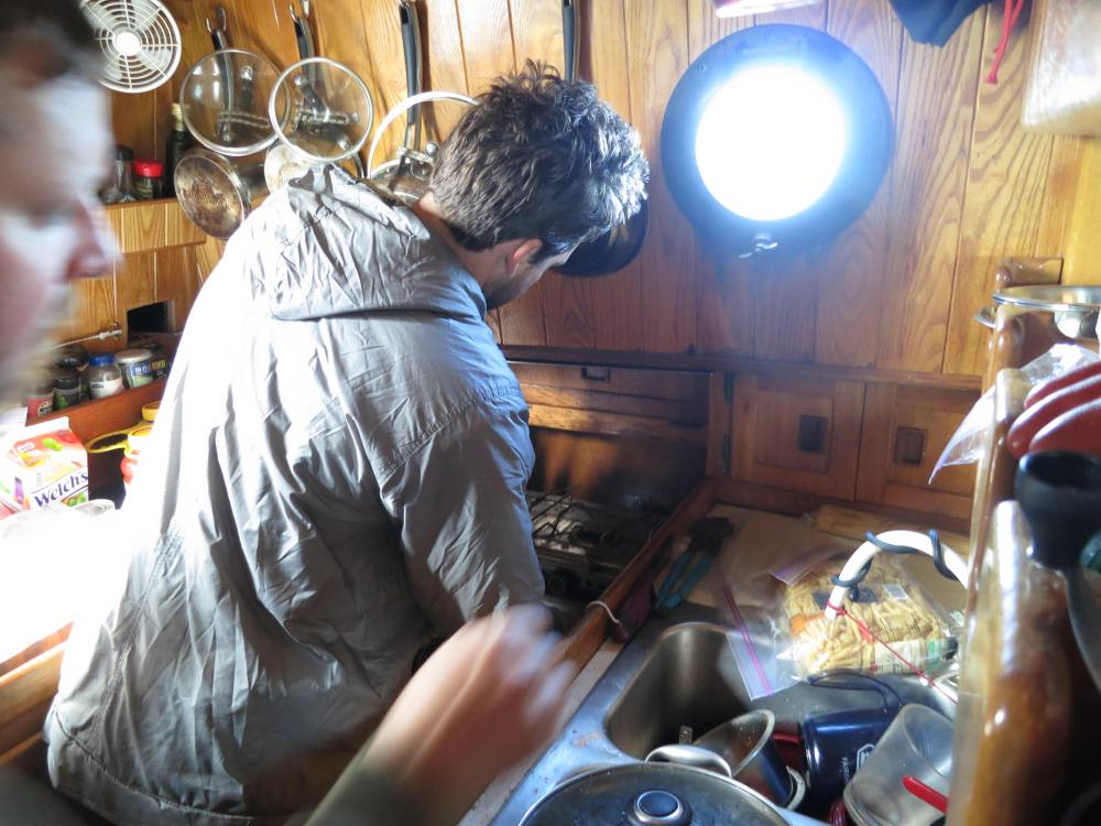 Jason Re works the galley plumbing, to maximize our fresh and salt water efficiency under way.
