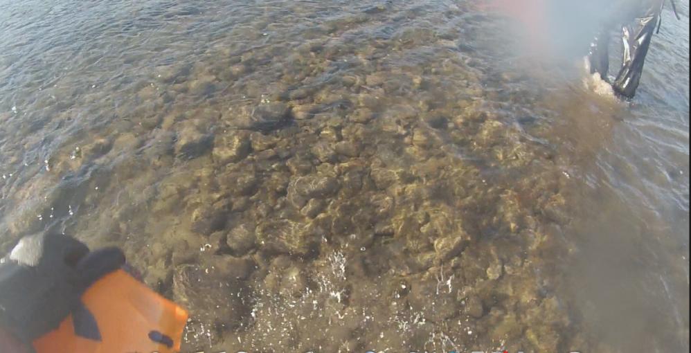 Walking the shallows behind Jason.  Broken helmet in hand.